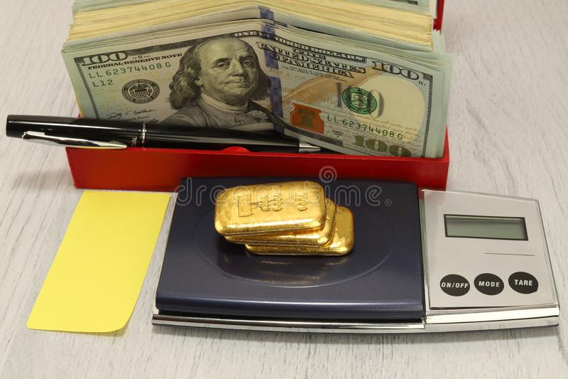 Op de schalen zijn drie bars van goud, naast het is een pak dollars Pen en blad van document Horizontale samenstelling, voorgrond stock afbeelding