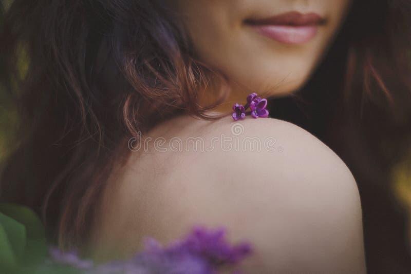 Op de schouder van een mooi meisje is er een lilac bloem van ultraviolette kleur stock foto