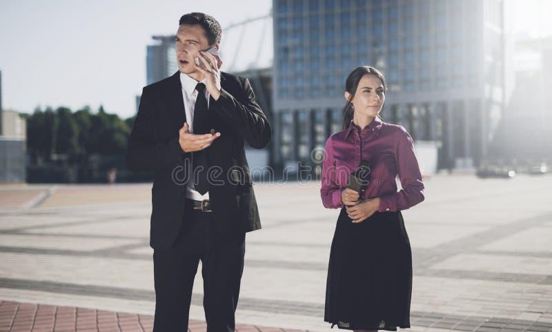 Op de straat spreekt een mens op iPhone, naast hem tribunes een journalist met een microfoon royalty-vrije stock foto