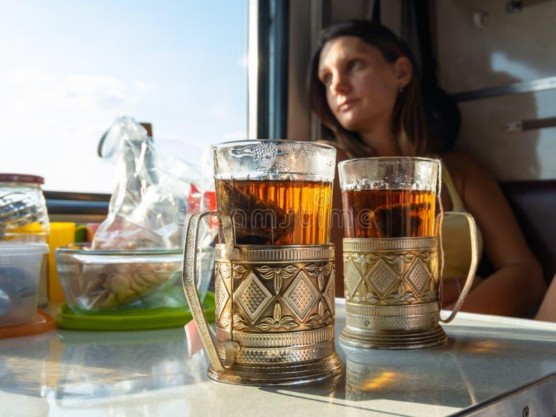 Op de tafel in het compartiment van de trein staan glazen met thee in metalen bekers, op de achtergrond ziet het meisje eruit.. royalty-vrije stock afbeeldingen