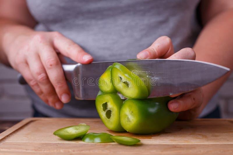 Op dieet zijnd, gezond voedsel, laag carburatordieet Overhandigt snijdende groene paprika, stock foto
