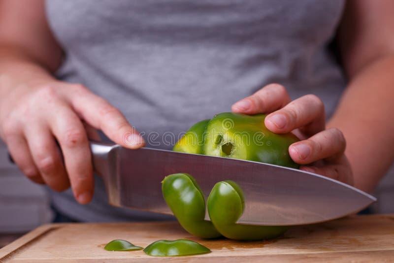 Op dieet zijnd, gezond voedsel, laag carburatordieet Overhandigt snijdende groene paprika, stock foto's