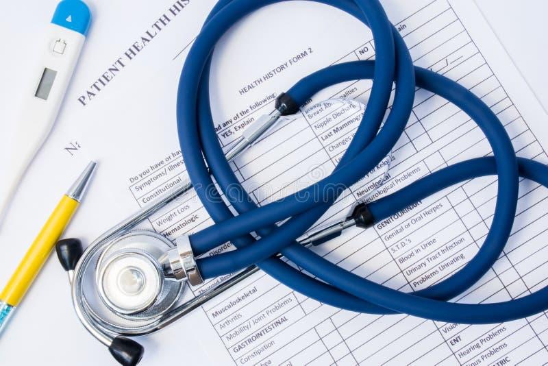 Op document geduldige gezondheidsgeschiedenis ligt de medische vragenlijstvorm artsen kenmerkende hulpmiddelen - stethoscoop en t royalty-vrije stock foto's