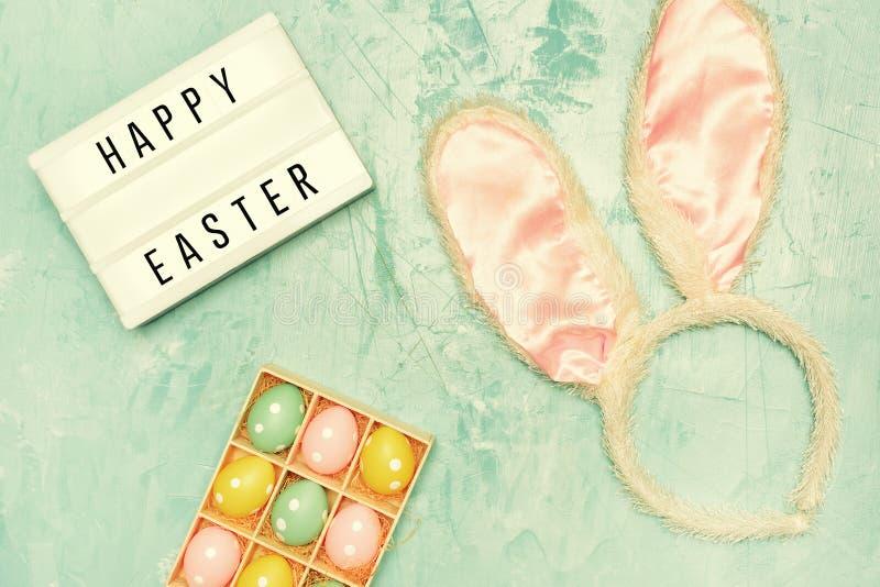 Op een blauwe achtergrond zijn paaseieren en oren van een konijnkostuum Lightbox met de inschrijving Gelukkige Pasen royalty-vrije stock foto's