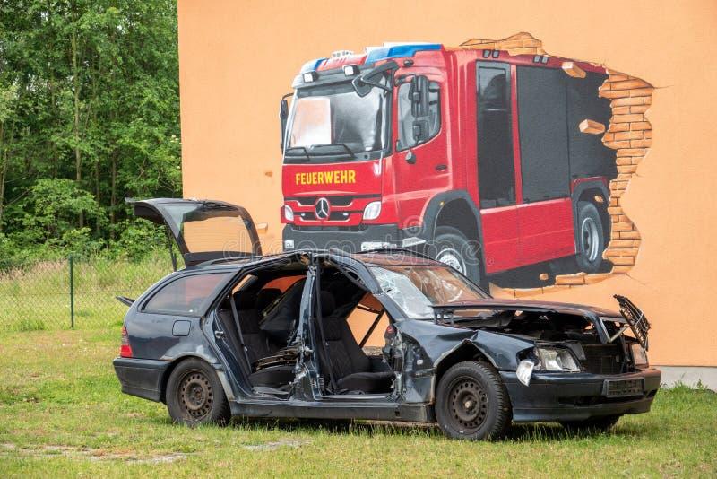 Op een gebouw van de brandbrigade is er een gesloopte auto royalty-vrije stock afbeelding
