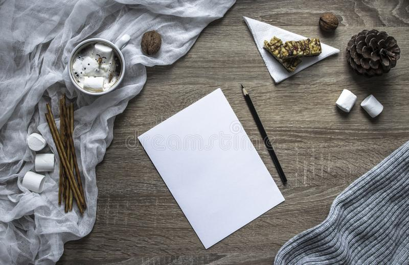 Op een houten achtergrond schrijven een blad en een pen heemst en de snoepjes, een mok met cacao ligt een gesmolten die sneeuwman stock foto