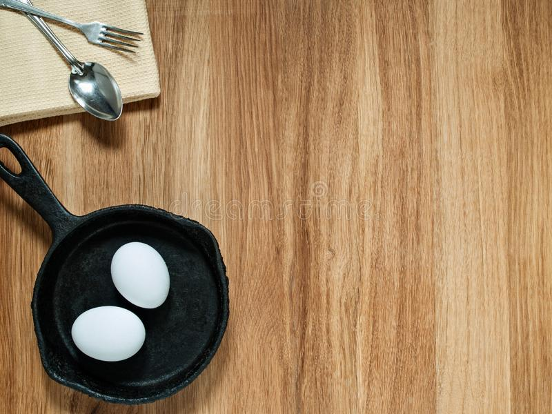 Op een houten achtergrond zijn een handdoek, lepel, vork, gietijzerpan, stock afbeelding