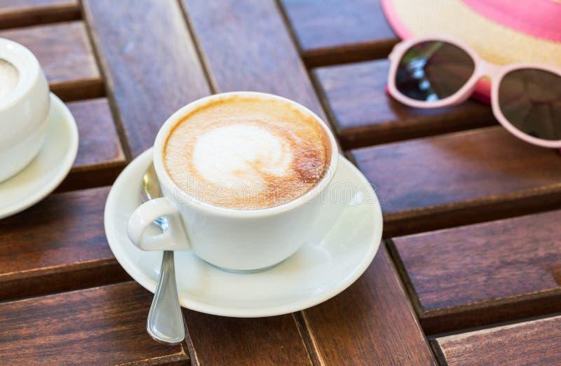 Op een houten bruine lijst is een kop met cappuccino, een hoed, glazen De zomer, koffie, rust stock foto