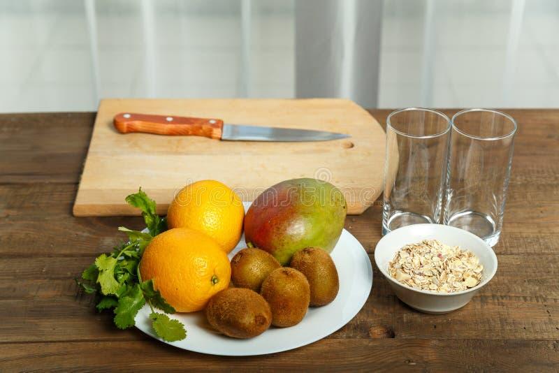 Op een houten lijst aangaande een witte plaat lig het de kiwifruit van mangosinaasappelen stock foto's