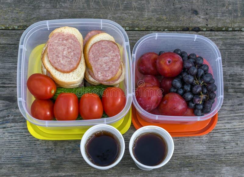 Op een houten lijst in een plastic container zijn groenten: tomaten en komkommers, evenals sandwiches met worst stock foto
