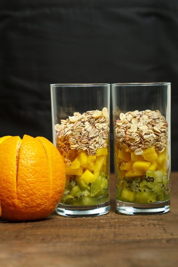 Op een houten lijst zijn twee glazen met stukken van fruit en muesli Verticale foto royalty-vrije stock fotografie