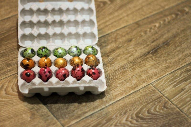 Op een houten verpakking als achtergrond van eieren verschillende kleuren Hoogste mening royalty-vrije stock foto's