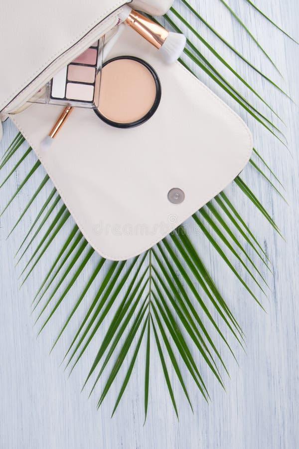 Op een lichte achtergrond en een groen blad van een palm, lig een open witte kosmetische zak met verspreide heldere make-uppunten stock fotografie