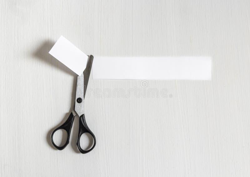 Op een lichte achtergrond sneed de schaar een stuk van document inschrijving af stock afbeelding