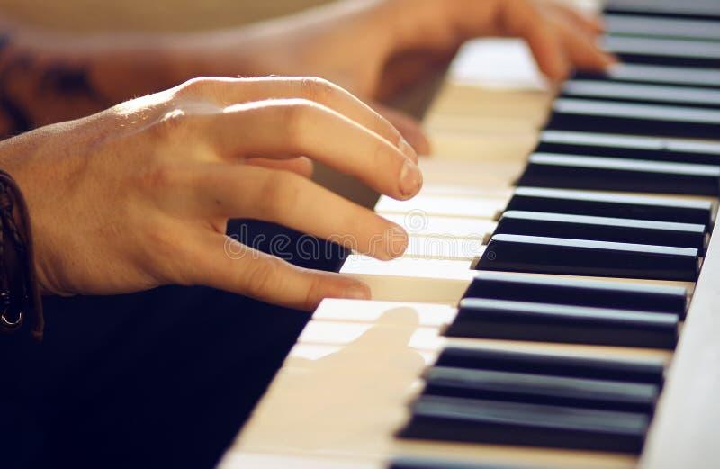 Op een muzikale mensenspelen van het toetsenbordinstrument een melodie met zijn handen royalty-vrije stock foto's