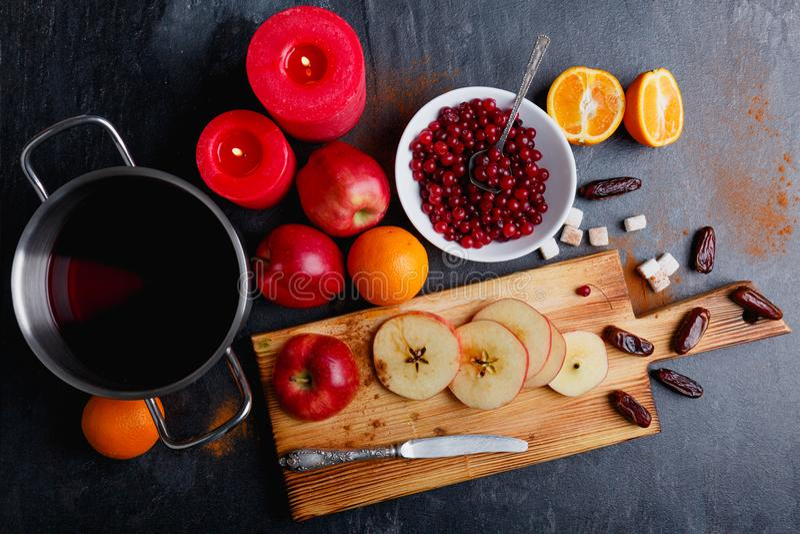 Op een oppervlakte zijn vruchten, data, pan met sangria, plaat met Amerikaanse veenbessen en brandende rode kaarsen stock foto