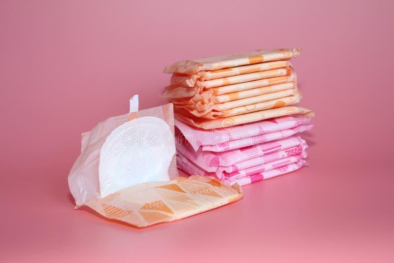 Op een roze achtergrond zijn verscheidene sanitaire stootkussens in individuele verpakking royalty-vrije stock fotografie