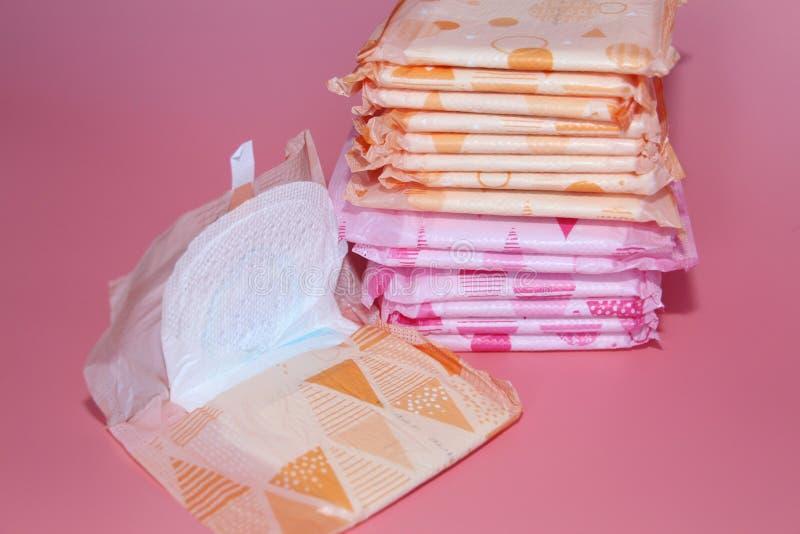 Op een roze achtergrond zijn verscheidene sanitaire stootkussens in individuele verpakking royalty-vrije stock foto
