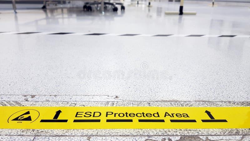 Op een vloer van de elektronika die kleeft het behandelde industriële linoleum een gele band met een standaardwaarschuwingstekst  stock afbeelding