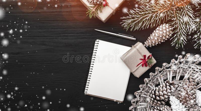 Op een zwarte achtergrond, een spar met kegel en decoratieve voorwerpen Gift en een notaboek of een Kerstmisbericht stock foto