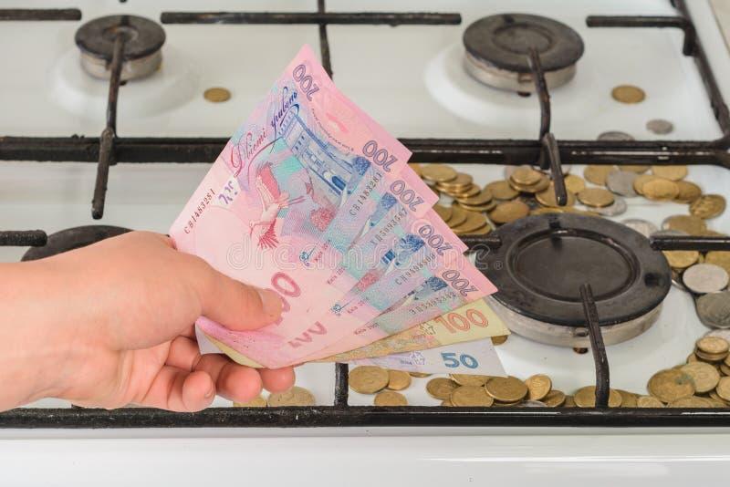 Op het gasfornuis zijn de muntstukken verspreid en een hand met een Oekra?ens bankbiljet is 200 hryvnias waard royalty-vrije stock afbeeldingen