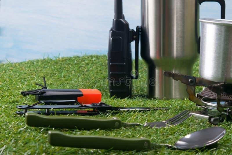 Op het gazon is er een brander voor het verwarmen van water en voedsel, een reeks van Bestek voor de keuken royalty-vrije stock foto