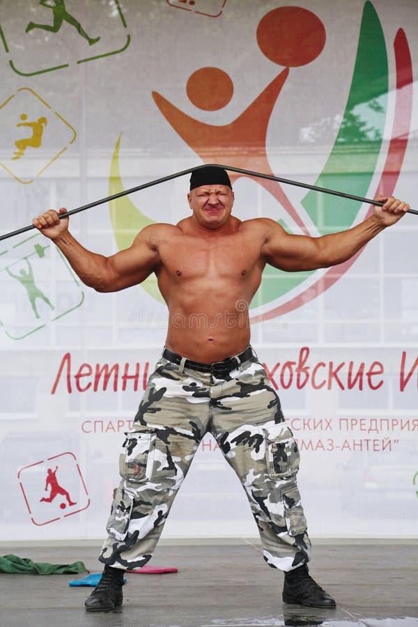 Op het stadium toon van kracht de metaal Russische ridder, strongman held verover, bodybuilder Sergey Sebald stock afbeeldingen