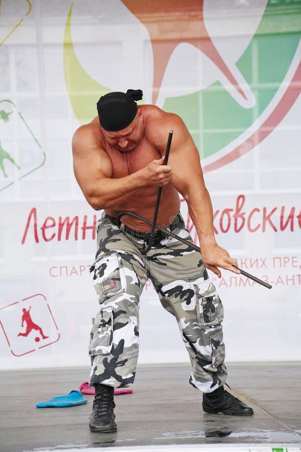 Op het stadium toon van kracht de metaal Russische ridder, strongman held verover, bodybuilder Sergey Sebald royalty-vrije stock foto's