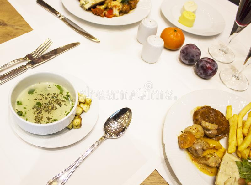 Op het tafelkleed is er een Kop van soep met kruiden, Franse frie stock afbeelding