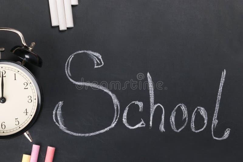 Op het zwarte schoolbord geschreven de woordschool met wit krijt en leugens de wekker stock foto's