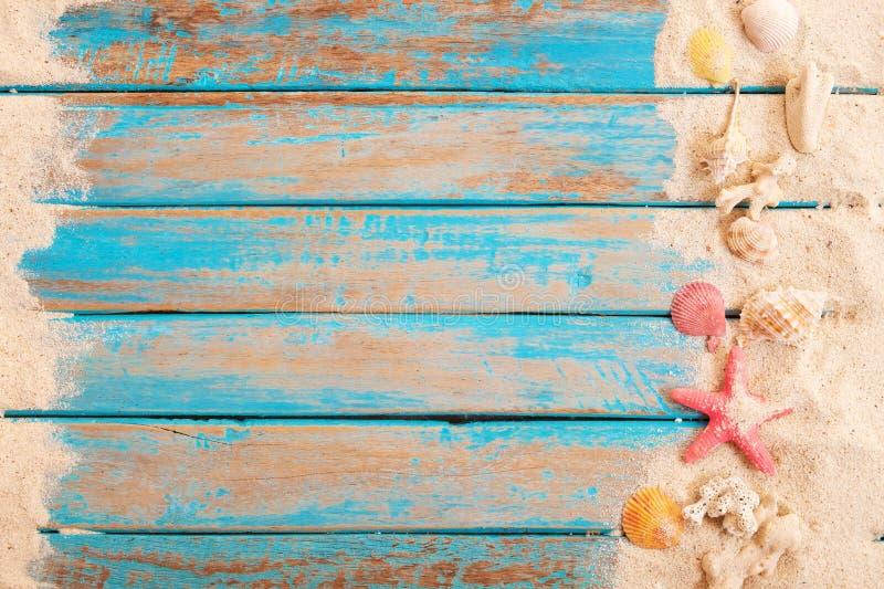 Op mening van strandzand met shells, zeester op houten plank in blauwe overzees royalty-vrije stock fotografie
