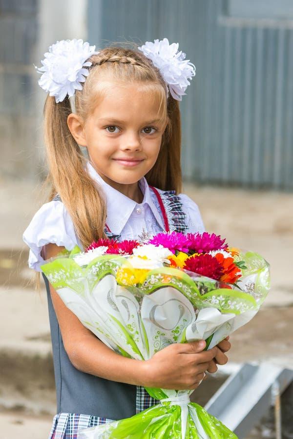 Op portret van een zevenjarig schoolmeisje met boeket van bloemen stock fotografie