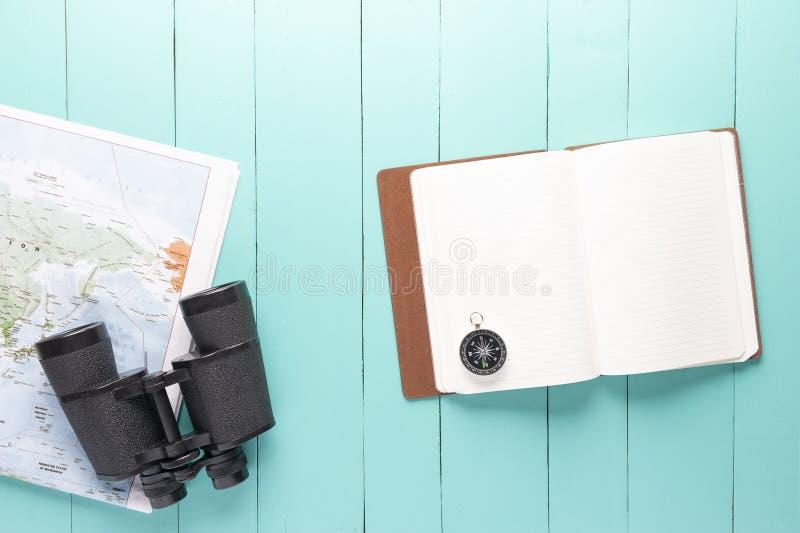 Op sikt av binokulärt, världskartan, kompasset och anteckningsboken på grön träbakgrund arkivbild