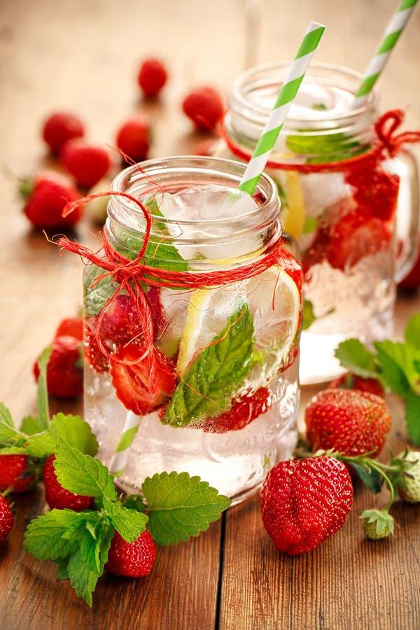 Op smaak gebracht water met verse aardbeien, citroen en munt stock fotografie