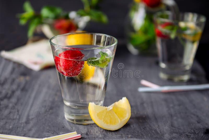 Op smaak gebracht water met verse aardbeien en munt in glas op een zwarte houten lijst met heldere details De selectieve nadruk,  royalty-vrije stock foto's
