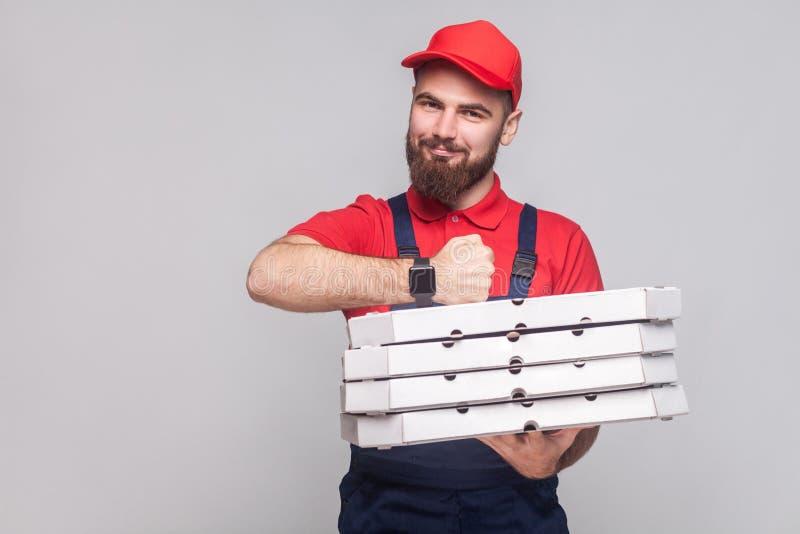 Op tijd! Jonge vrolijke leveringsmens met baard in blauwe eenvormig royalty-vrije stock foto