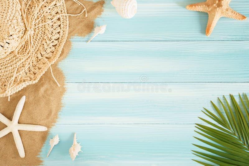 Op widok denny słomiany kapelusz i morze łuska na dennym piasku na błękitnym drewnianym tle, lata pojęcie na pustym Palmowego liś zdjęcia stock