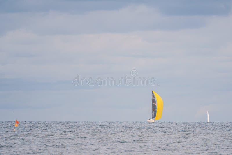 Op zee drijft een zeilboot met een felgele zeilboot en de lucht zit vol wolken stock fotografie