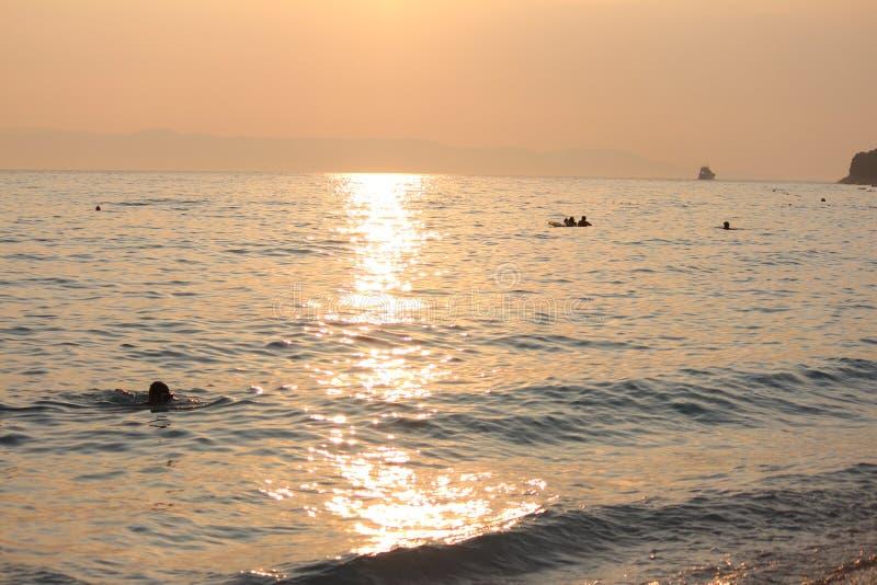 Op zee zonsondergang, jaarlijkse onderbrekingen, die zwemmen en stock foto