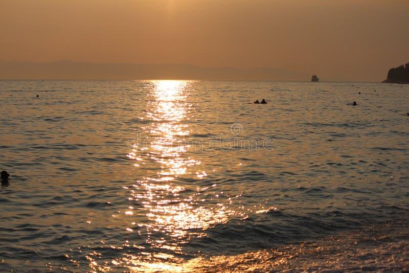 Op zee zonsondergang, jaarlijkse onderbrekingen, die zwemmen en royalty-vrije stock afbeeldingen