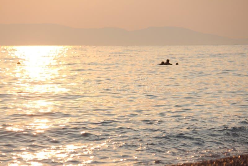 Op zee zonsondergang, jaarlijkse onderbrekingen, die zwemmen en stock afbeeldingen