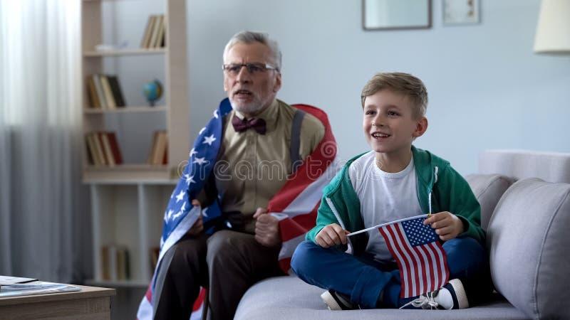 Opa in Amerikaanse vlag het letten op sport met jongen wordt verpakt, die zich over spel ongerust maken dat stock afbeelding