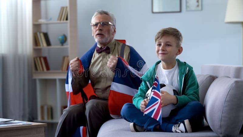 Opa in Brits vlag het letten op voetbal met jongen wordt verpakt, die zich over spel ongerust maken dat royalty-vrije stock foto