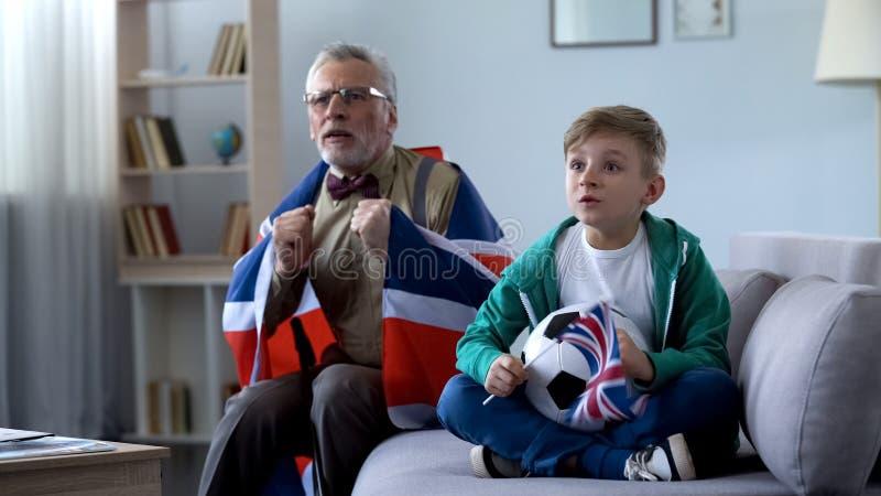 Opa in Brits vlag het letten op voetbal met jongen wordt verpakt, die zich over spel ongerust maken dat stock foto's