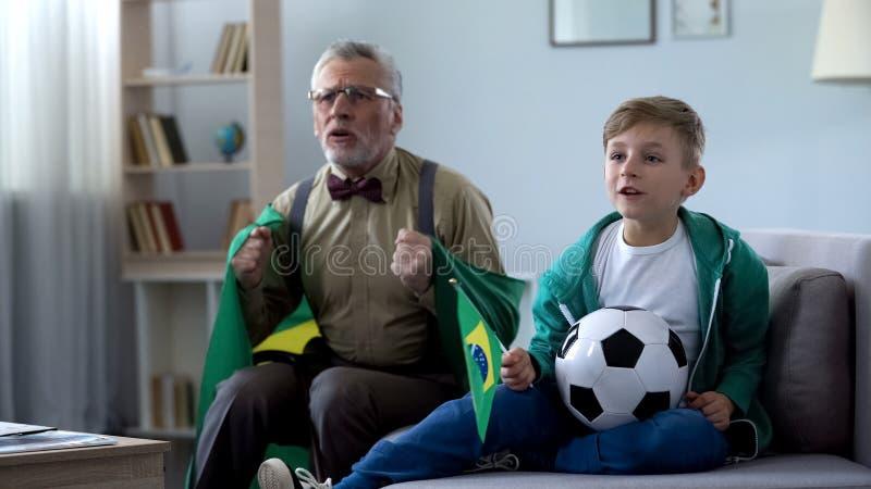 Opa in de vlag van Brazilië het letten op voetbal met jongen wordt verpakt, die zich over spel ongerust maken dat royalty-vrije stock foto