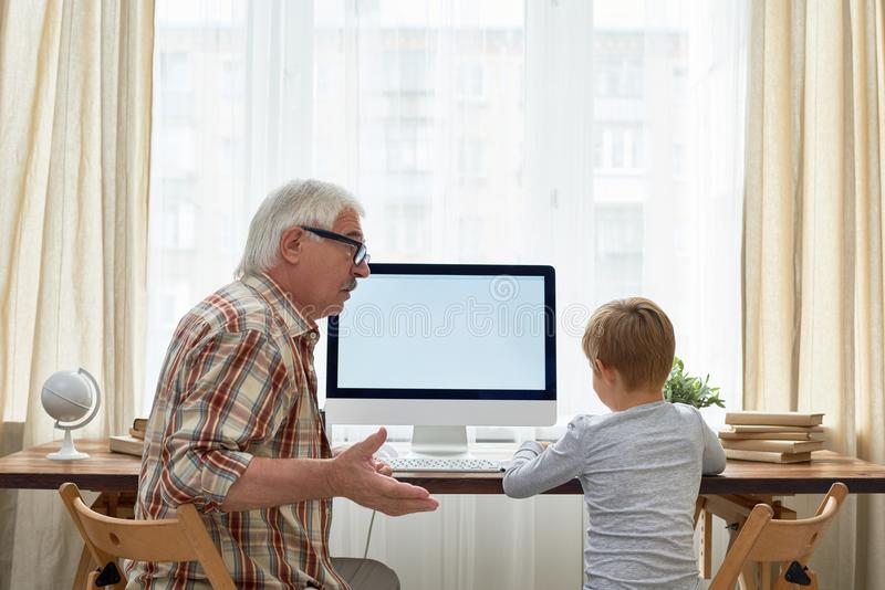 Opa die Jongen met Thuiswerk helpen royalty-vrije stock foto