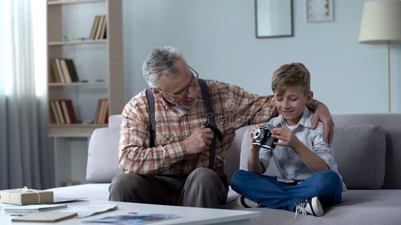 Opa die kleinzoon verklaren hoe te om retro camera, jonge fotograafdromen te gebruiken royalty-vrije stock afbeelding