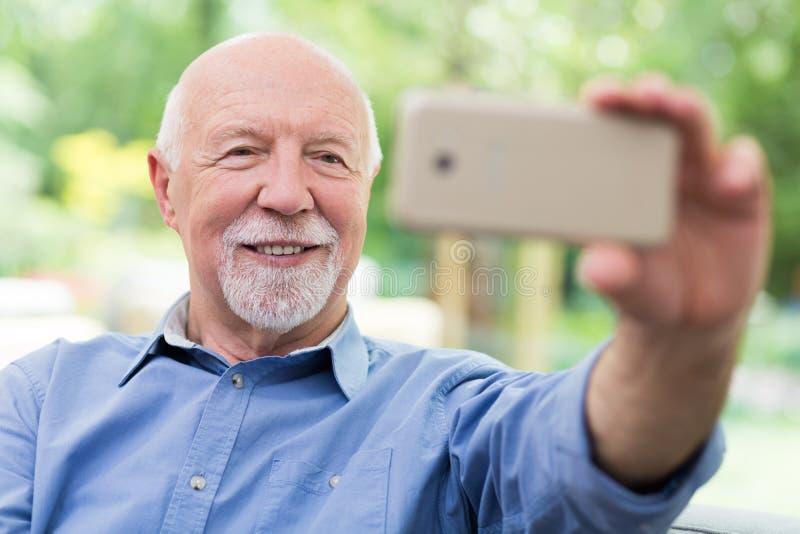 Opa die zichzelf neemt met zijn mobiele telefoon royalty-vrije stock afbeelding