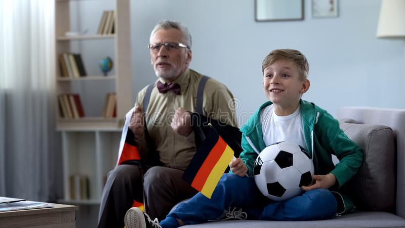 Opa in Duitse vlag het letten op voetbal met jongen wordt verpakt, die zich over spel ongerust maken dat stock afbeeldingen