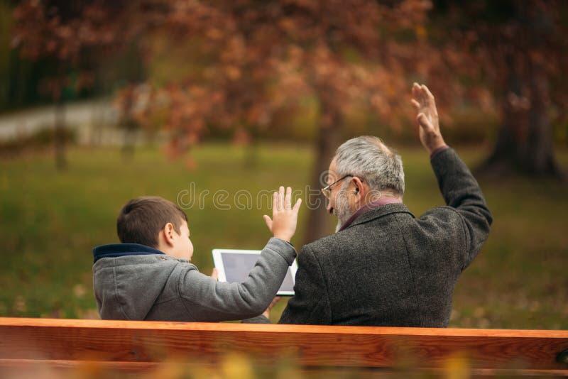 Opa en kleinzoon de zetel op de bank en gebruikt een tablet Zij steken omhoog hun hand op stock afbeelding